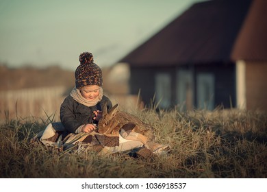 Cute little girl is playing with a rabbit in the country, Russia. Image with selective focus and toning.