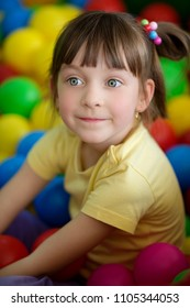 Cute little girl in the playing room with  colorful balls