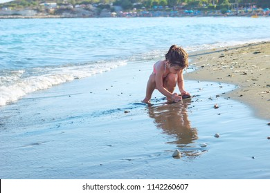 Cute Little Girl playing with sand by the Sea Waves.  Summer Sunny Day, Ocean Coast