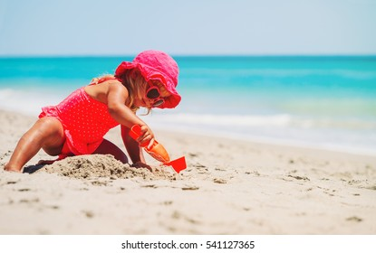 cute little girl playing with sand at beach