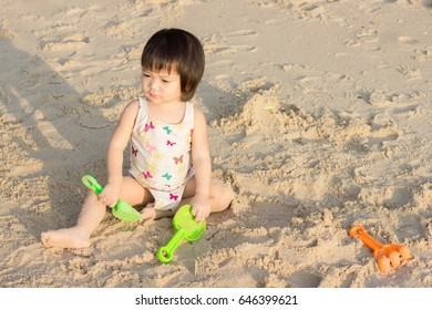 Cute little girl playing with sand toy on the beach.
