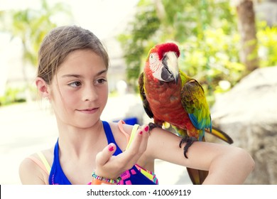 Cute little girl playing with a Scarlet Macaw Parrot while on cruise vacation in Mexico.