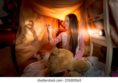 Cute little girl playing in shadow theater in bedroom at night