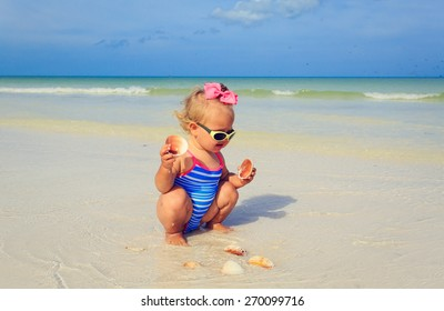 cute little girl playing with shells on summer beach