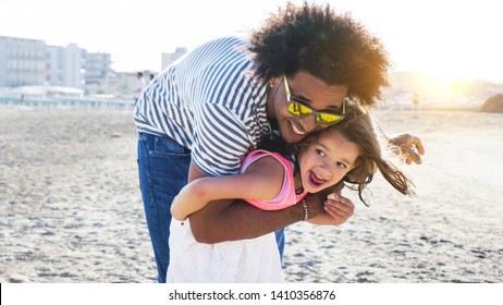 cute little girl playing and smiling with afro hair father on beach. mixed race child with young black parent. concept of diversity and family fun.