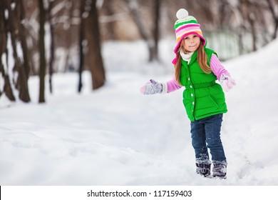 Cute little girl playing snowballs