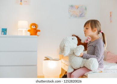 Cute little girl playing with soft toy at home