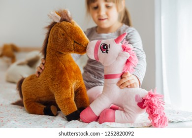 Cute little girl playing with soft toys at home