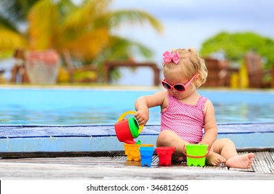 cute little girl playing in swimming pool at tropical beach