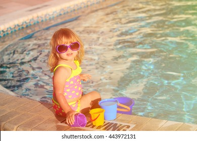 cute little girl playing in swimming pool at beach