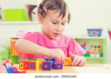 Cute little girl playing with toy bricks at school