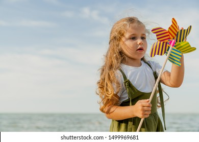 Cute little girl playing with windmill on the sunny beach