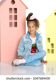 A cute little girl is playing with wooden houses. The concept of family happiness, play, creative development of the child.