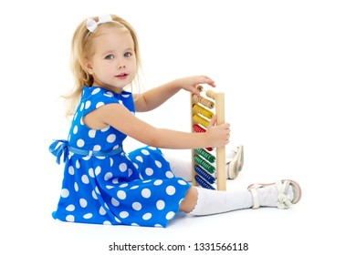 Cute little girl is playing with wooden abacus at home. An intelligent child learns to count. She enjoys with an educational toy at home or in kindergarten. Isolated on white background.