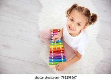 Cute little girl playing with xylophone  at home