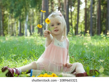 Cute little girl playing with yellow flowers in a summer park