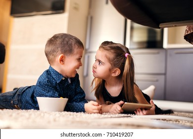 Cute little girl with ponytails looking strange at her brother.