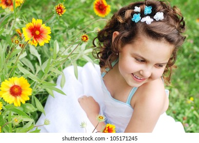Cute little girl portrait on the green meadow with yellow flowers
