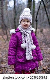 Cute little girl posing in autumn forest.