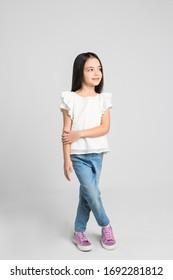 Cute little girl posing on light grey background