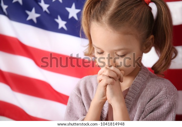 Cute little girl praying for America and flag on background