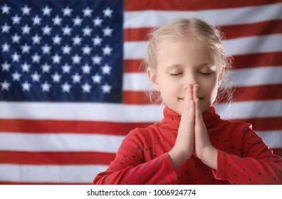 Cute little girl praying on American flag background