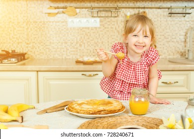 Cute little girl prepare pancakes and pouring honey on stack of pancakes in the kitchen.