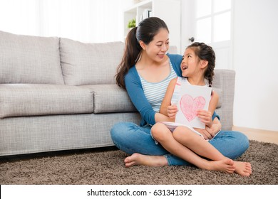 cute little girl prepared mother's day card ready give young woman when sitting on the living room floor together and looking at each other.