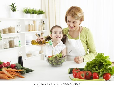 Cute little girl  preparing salad with her mom