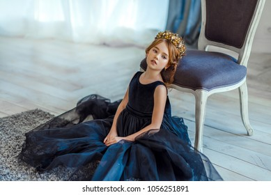 Cute little girl in a princess costume. Pretty child preparing for a costume party. Beautiful queen in gold crown and elegant dress.