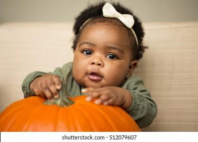 Cute little girl with a pumpkin.