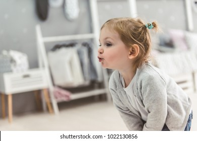 Cute little girl is pursing her lips while playing in the children's room