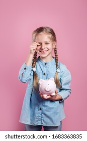 Cute little girl putting coin into piggy bank on pink background
