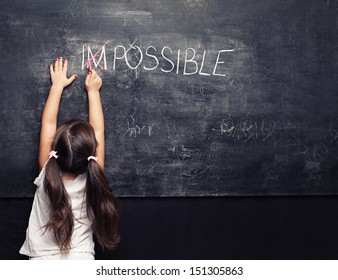 cute little girl putting a cross over impossible on blackboard