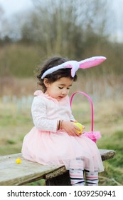 A cute little girl with rabbit ears hairband looking an easter egg while sitting on a bench.