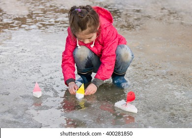 Cute little girl in rain boots playing with ships in the spring water puddle