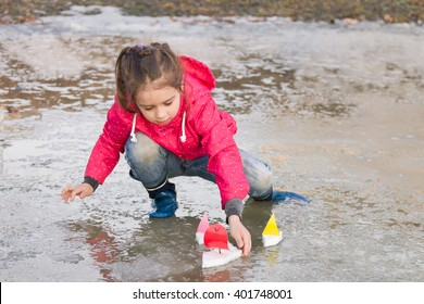 Cute little girl in rain boots playing with colorful ships in the spring creek standing in water outdoors