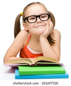 Cute little girl is reading book wearing glasses, isolated over white