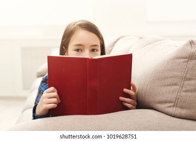 Cute little girl reading a book, covering half face with it. Young cute woman studying at home, sitting on couch, copy space