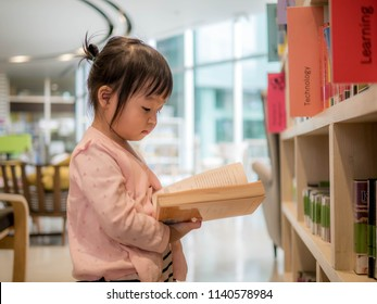 Cute little girl reading book in the library, this image can use for education