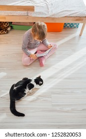 Cute little girl reading book sitting with cat at home