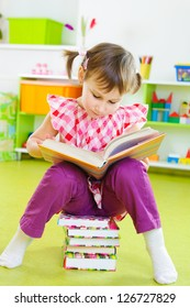 Cute little girl reading book sitting on stack of book