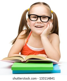 Cute little girl is reading a book while wearing glasses, isolated over white