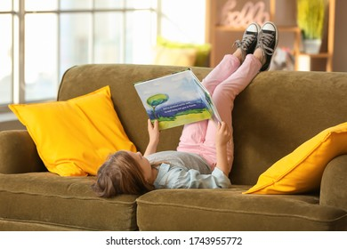 Cute little girl reading book on sofa at home
