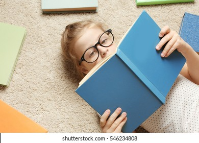Cute little girl reading book while lying on carpet