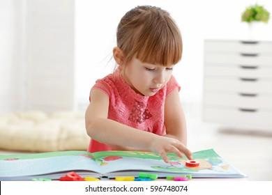 Cute little girl reading book at speech therapist office