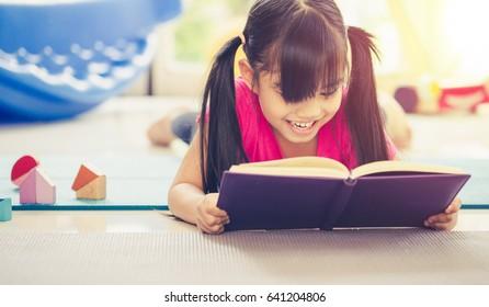 Cute little girl is reading a book . Funny kid having fun in kids room