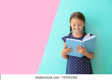 Cute little girl reading book on color background