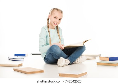 cute little girl reading book and smiling at camera isolated on white