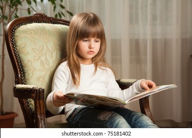Cute little girl reading a book at home